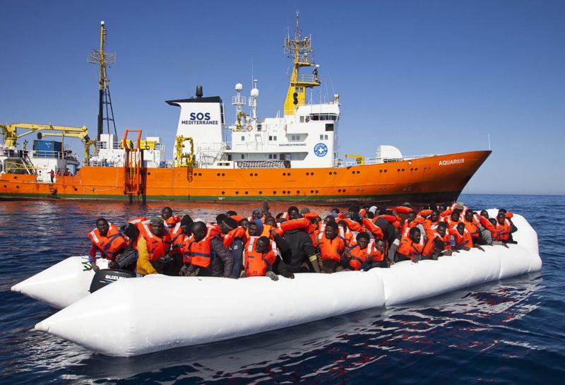 Una lancha con inmigrantes africanos y, detrás, el barco de SOS Méditerranée