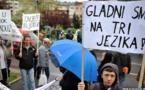 """Manifestantes bosnios con los carteles donde se lee """"tenemos hambre en tres idiomas"""""""