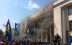 El humo de la granada sube, entre los manifestantes y los policías, delante del parlamento