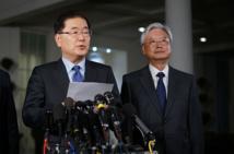 Chung Eui-Yong-a la izquierda-da la noticia ante la casa blanca.